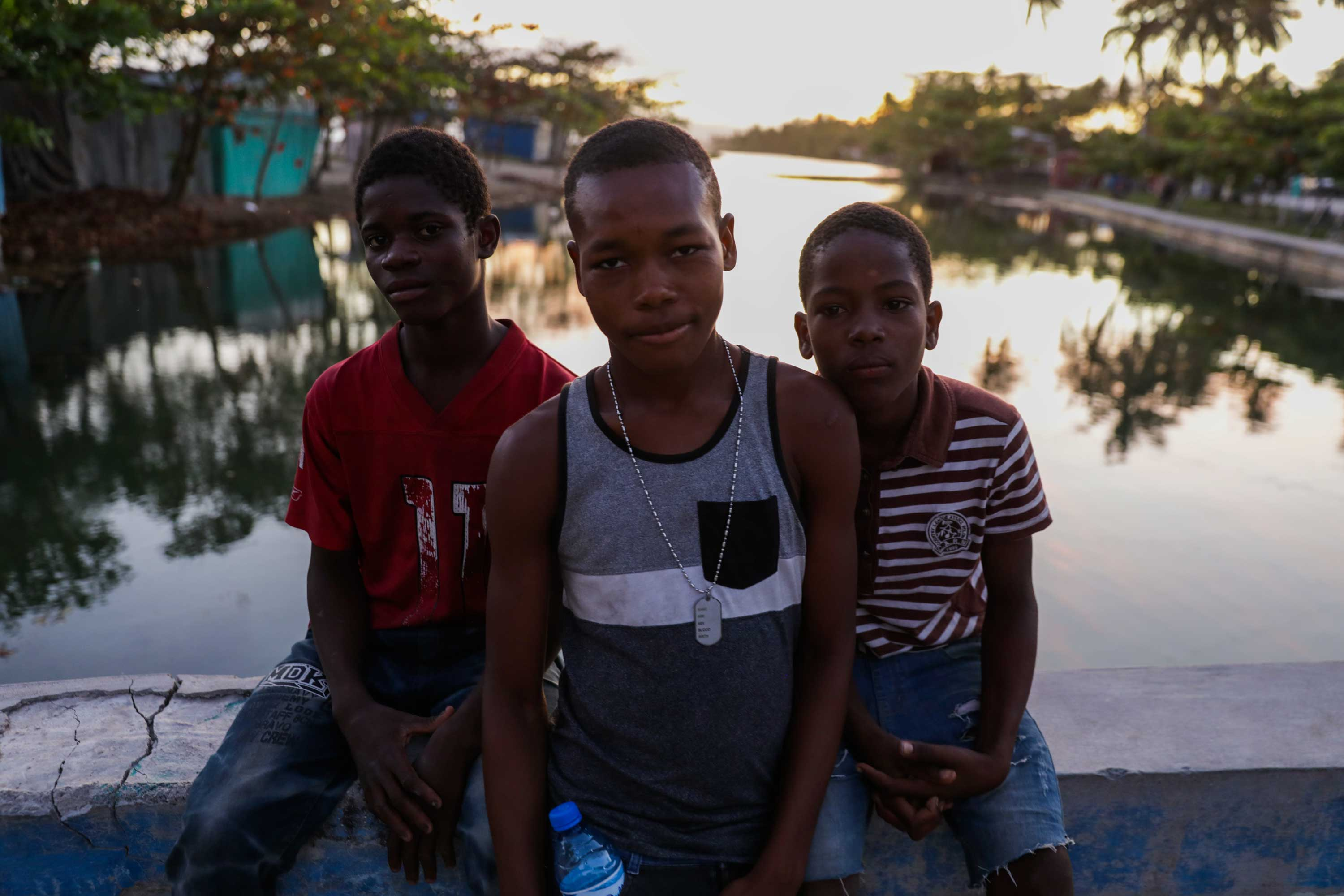 Three boys sitting on the bridge at Gelée Beach, Haiti