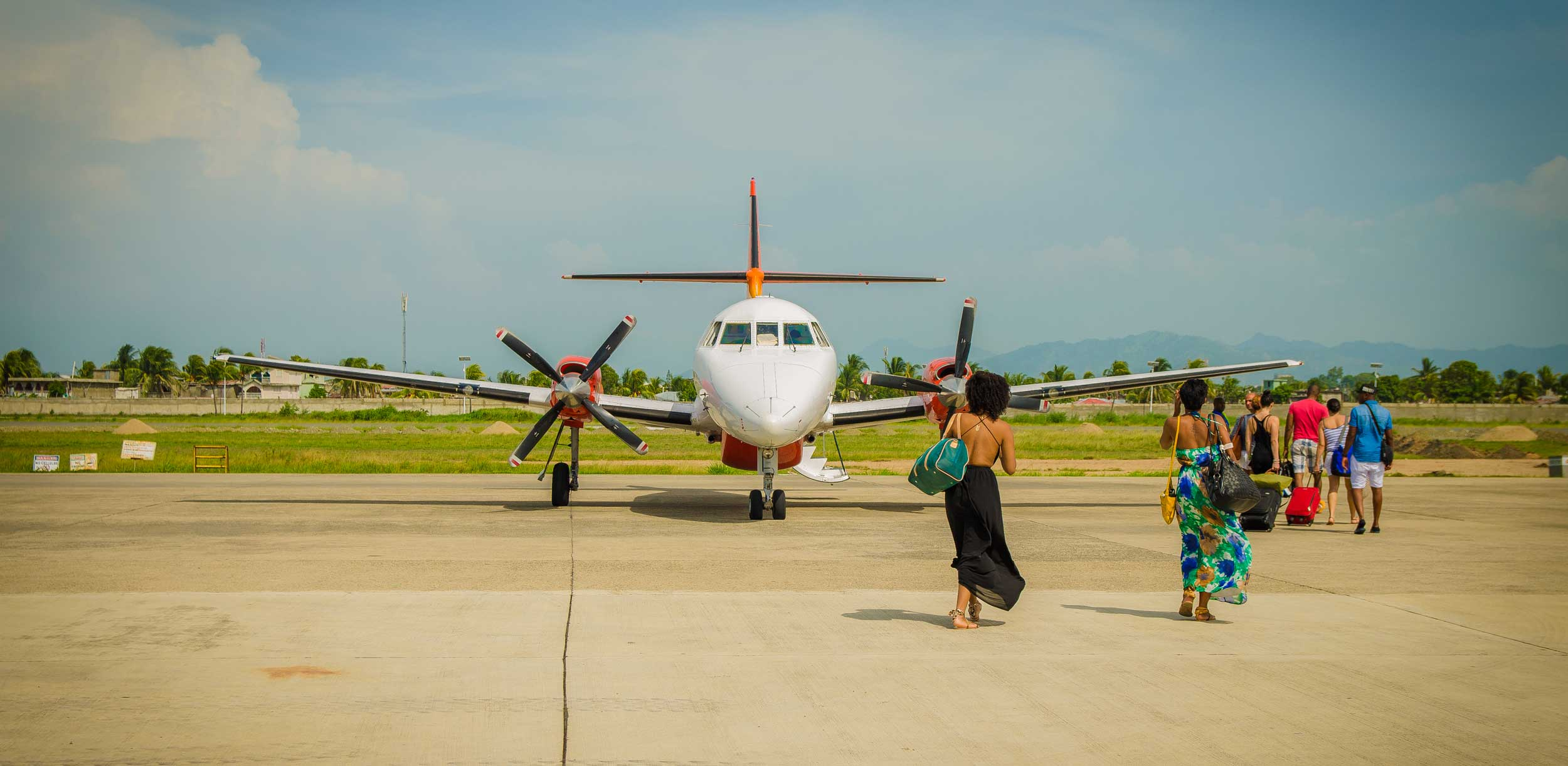 Women in dresses crossing the airstrip to board a plane at Aerogare Guy Malary, Port-au-Prince, Haiti