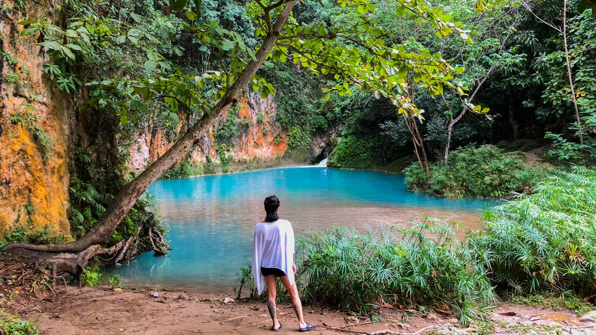 Woman stands on the bank of a bright blue pool at Bassin Bleu, Haiti