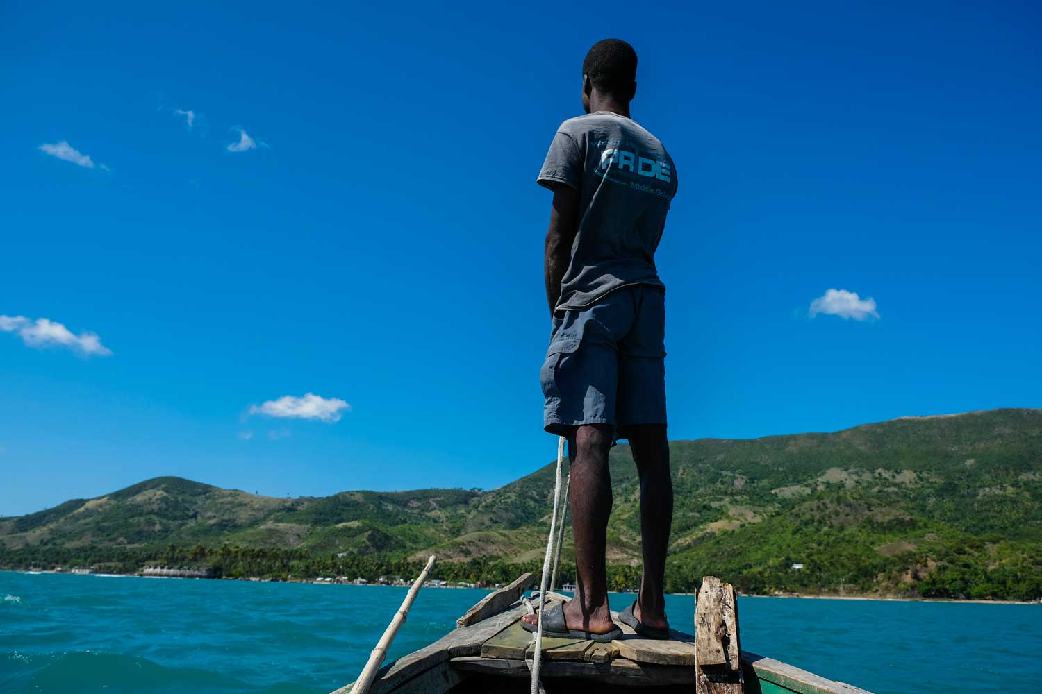 Person stands on the bow of a boat to Fort des Anglais, Haiti