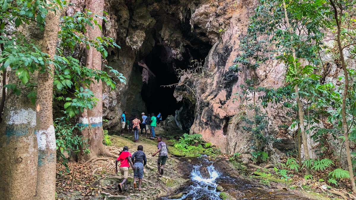 Group of people walking up to the entrance of the caves at Bassin Zim, Haiti