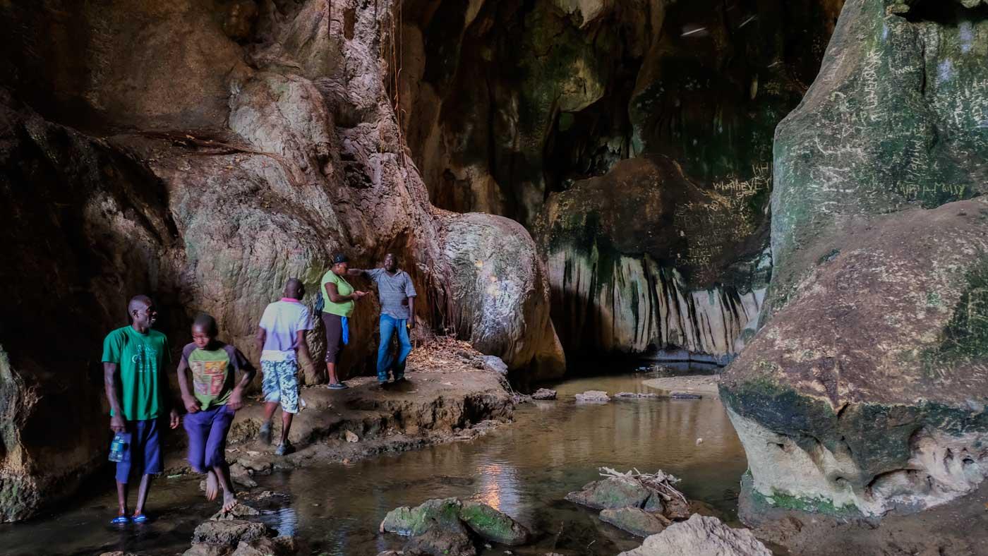 Five people walking across rocks inside the grotto of Bassin Zim, Haiti