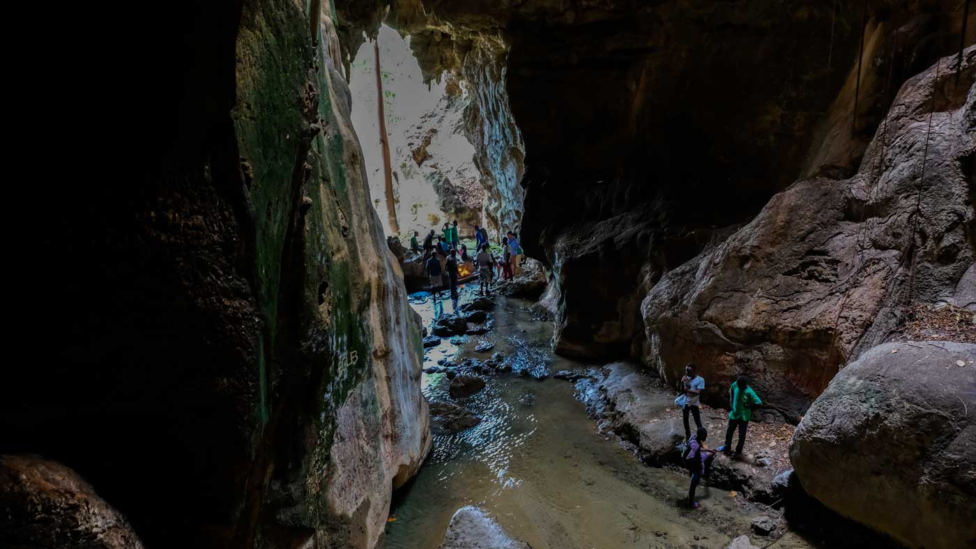 Group of people walking through the caves at Bassin Zim, Haiti