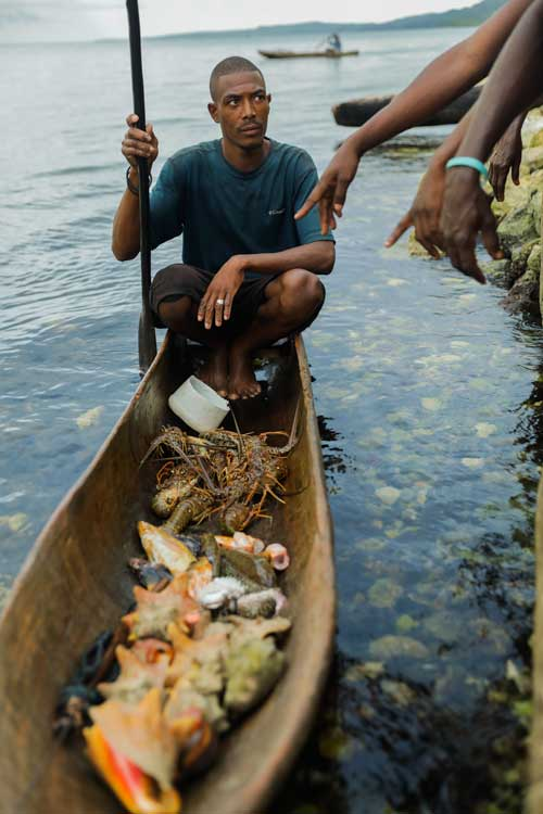 Haitian fisherman with his catch in a traditional boat near Pestel, Haiti