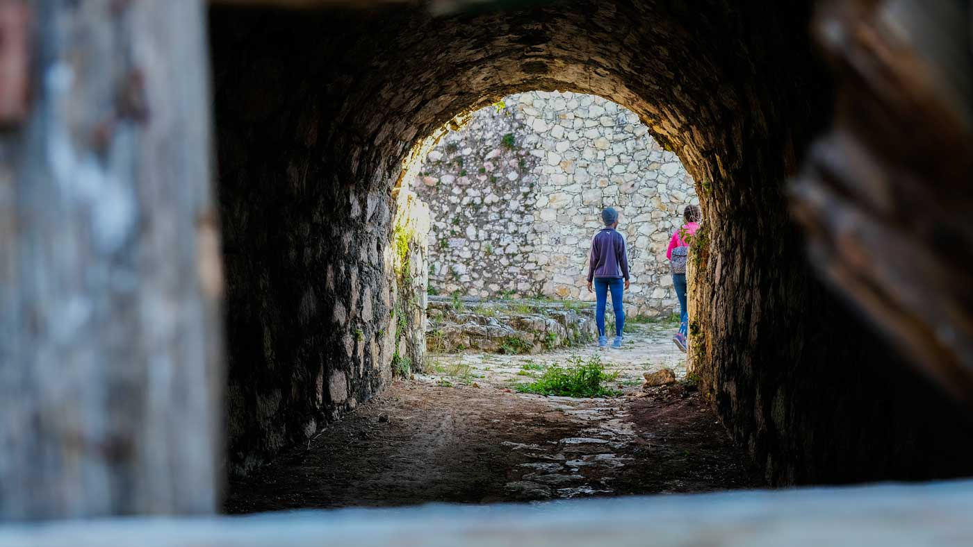 Two people seen through a dark tunnel at Fort Jacques, Haiti