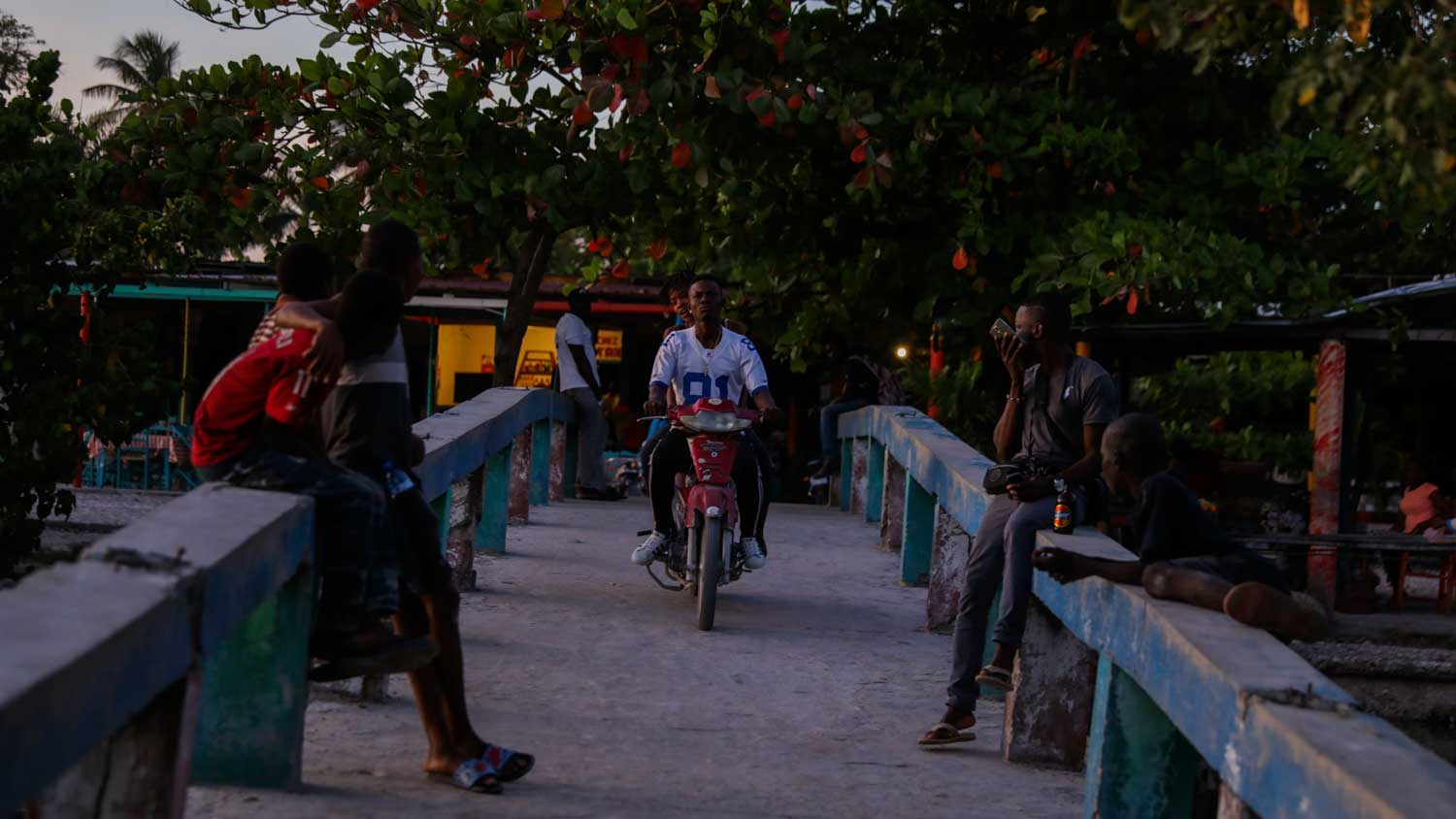 People relaxing at dusk on the boardwalk by Gelée Beach, Haiti