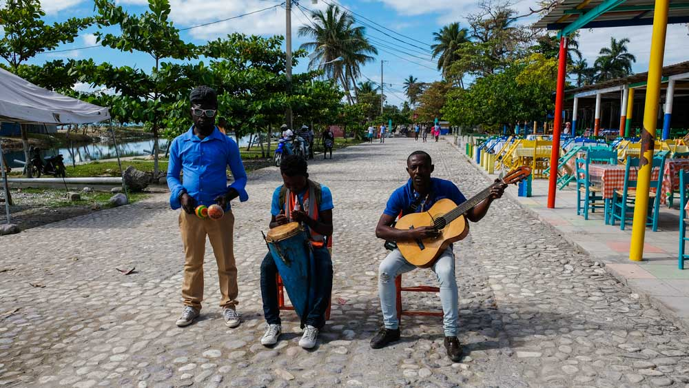 Three musicians performing on the boardwalk by Gelée Beach, Haiti