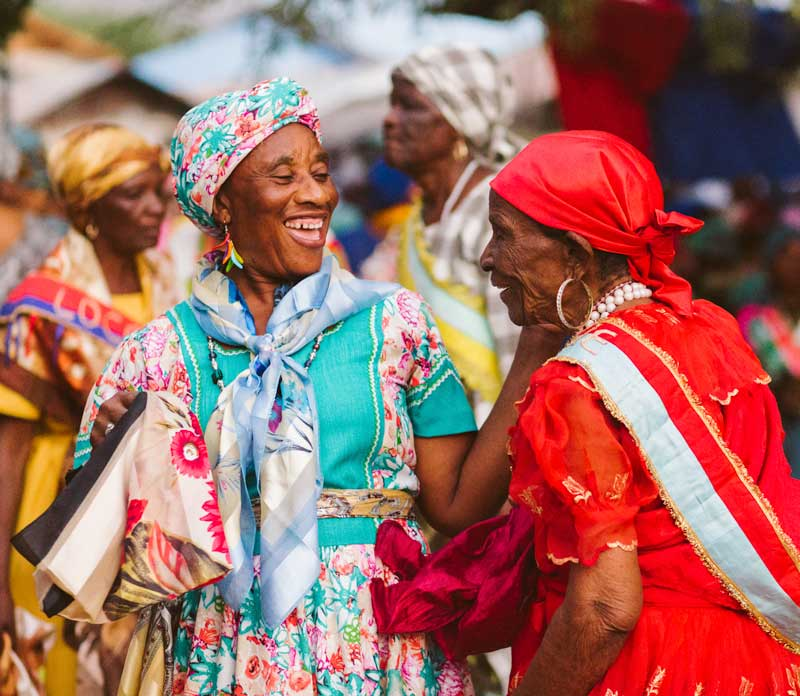 Four laughing Haitian women in traditional costume