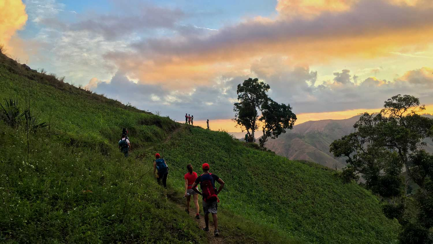 People hiking across a hill in Grandou, Haiti