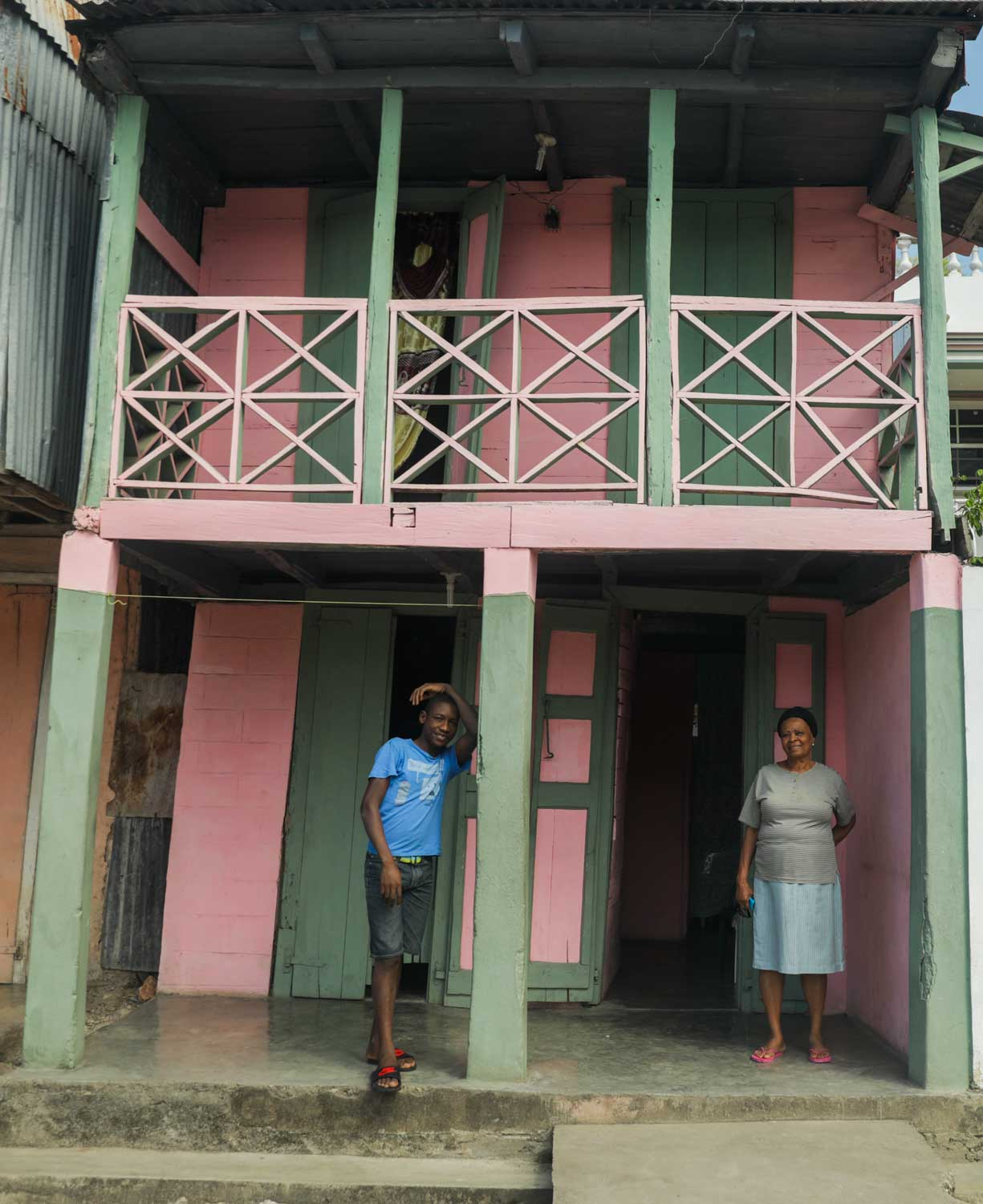 Two people stand smiling in front of a pink and green painted wooden house in Baradères, Haiti