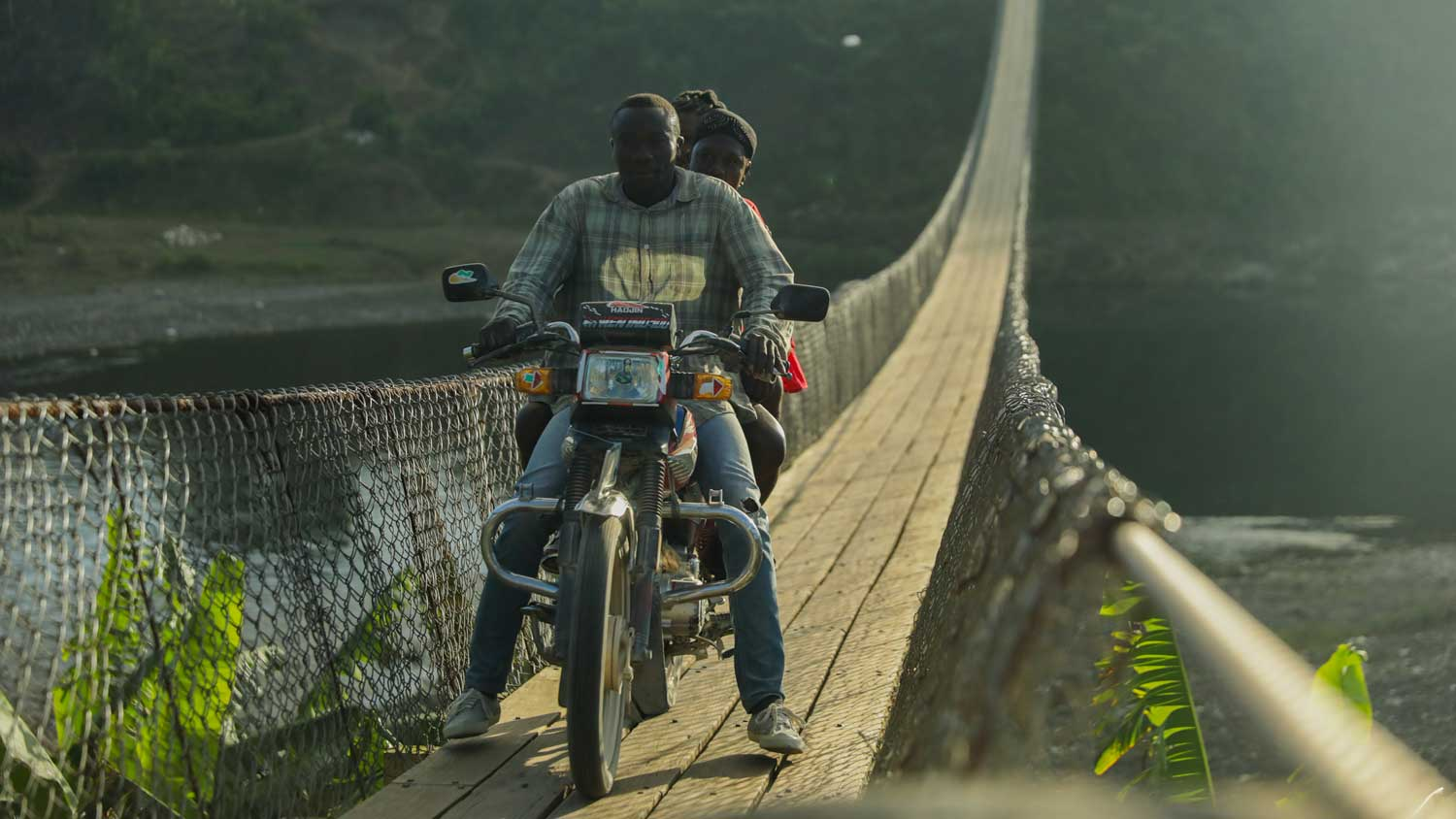 Moto driver crossing suspension bridge in Haiti