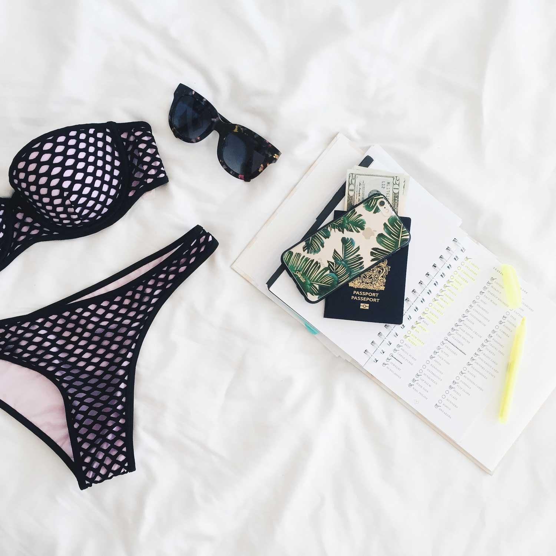Flatlay of beachwear, diary and passport ready for vacation