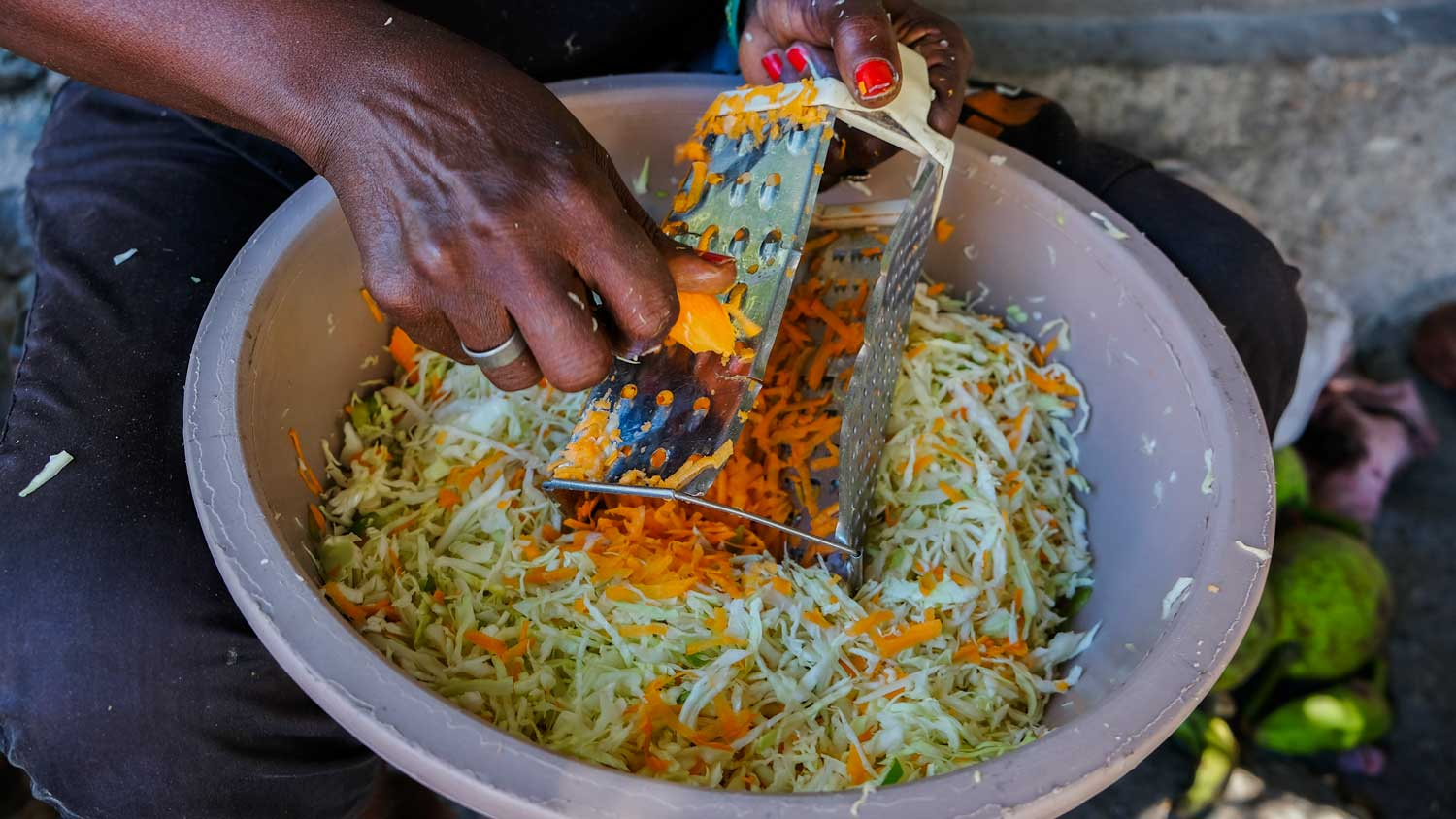 Woman making pikliz at a market in Jacmel, Haiti