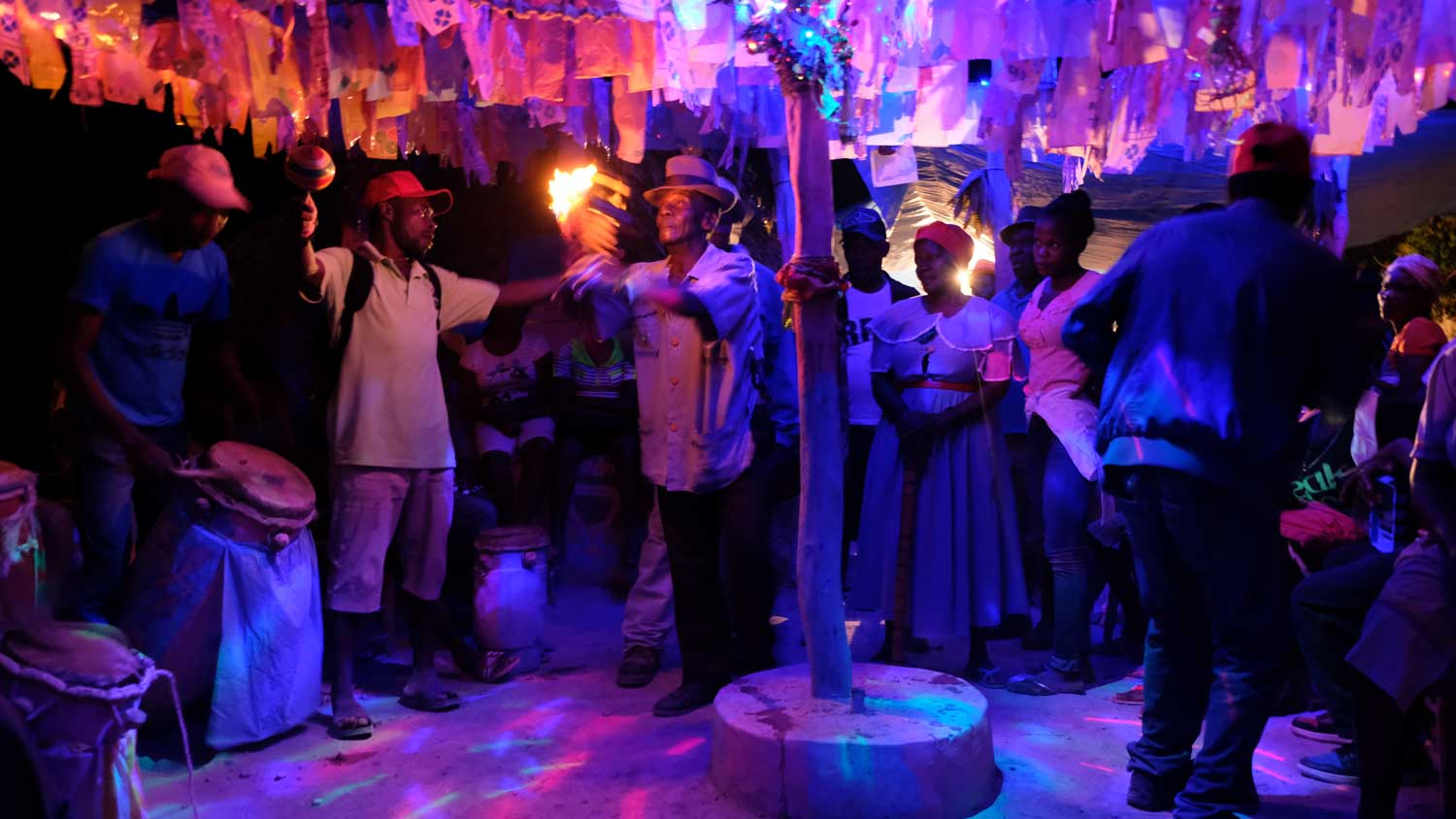 People gather around for a Vodou ceremony inside a Haitian Vodou temple in Petavie