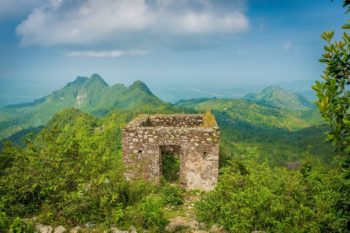 Photo of ruined fortress outpost with miles of jungle-covered mountain range in background, near Milot, Haiti