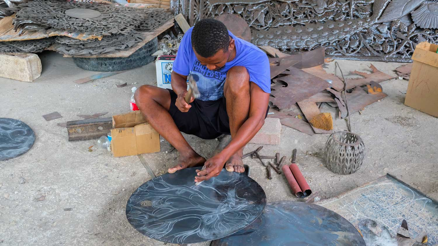 Blacksmith hammers design into metal artwork in Village Noailles, Haiti