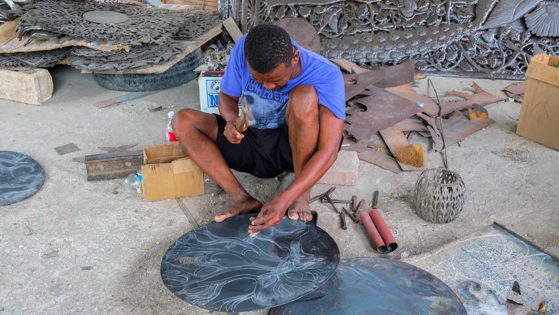 Blacksmith hammers design into metal artwork in Village Noailles, Haiti