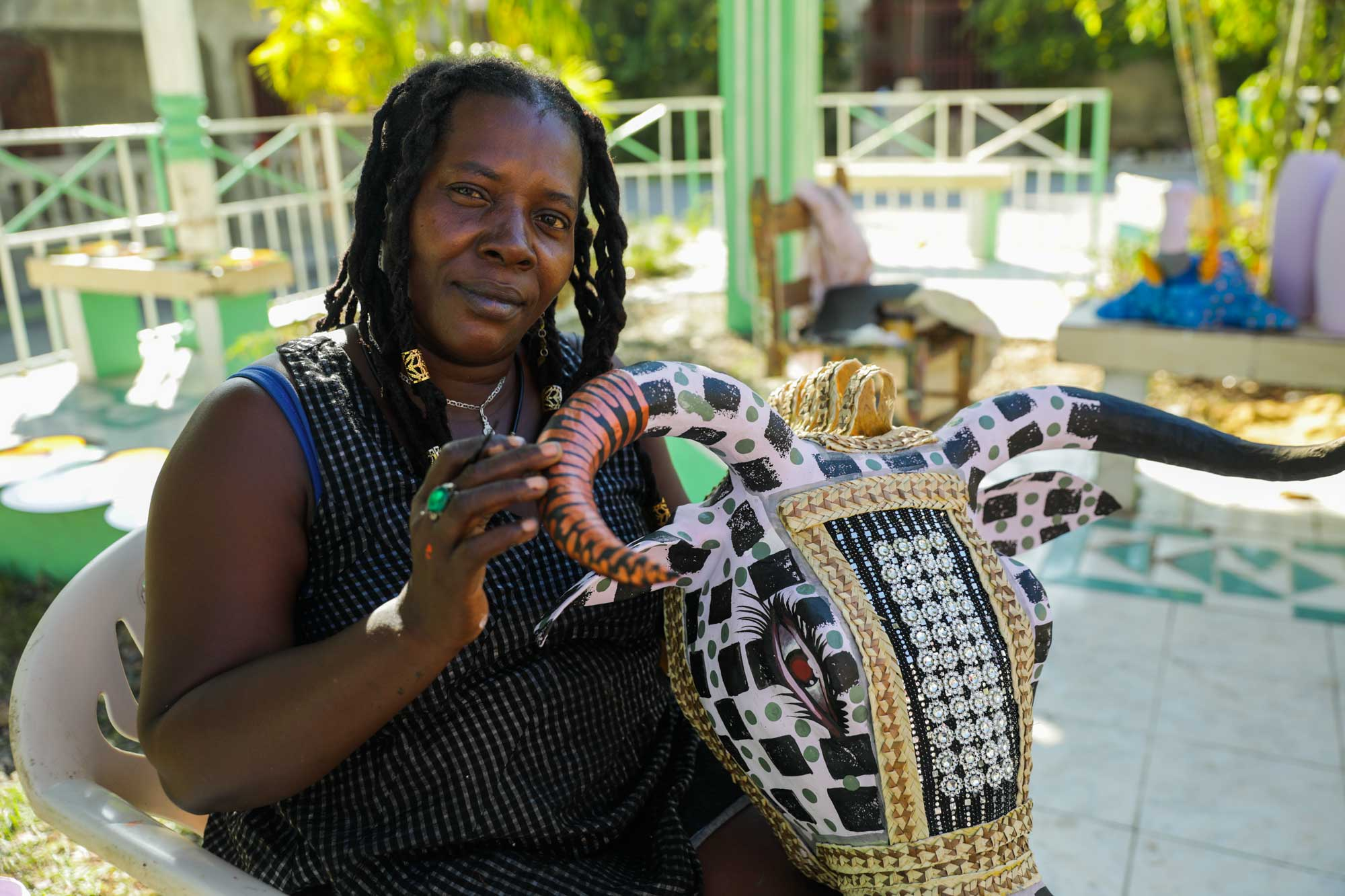 Paper mâché artist Charlotte shows off an intricate cow mask in Jacmel, Haiti