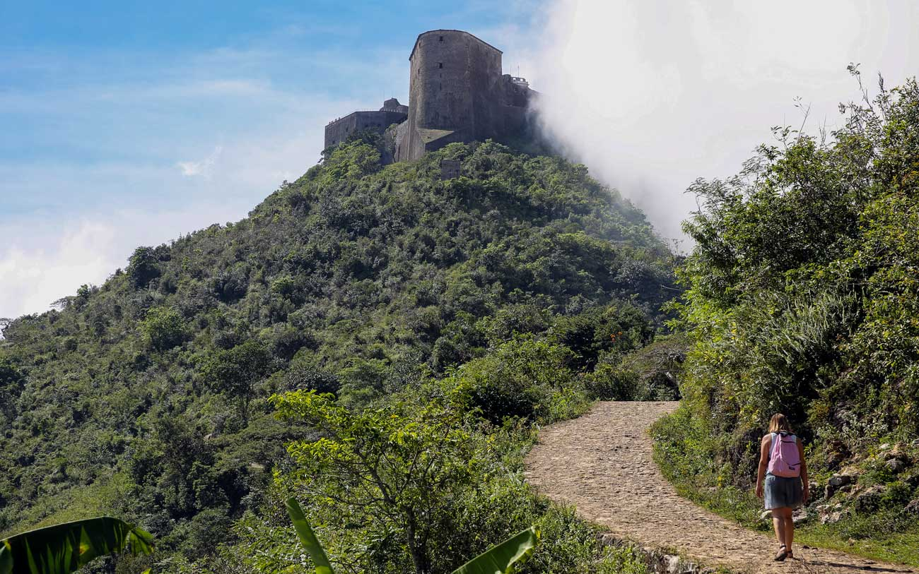 A woman hikes up the path to Citadelle Laferrière, Haiti