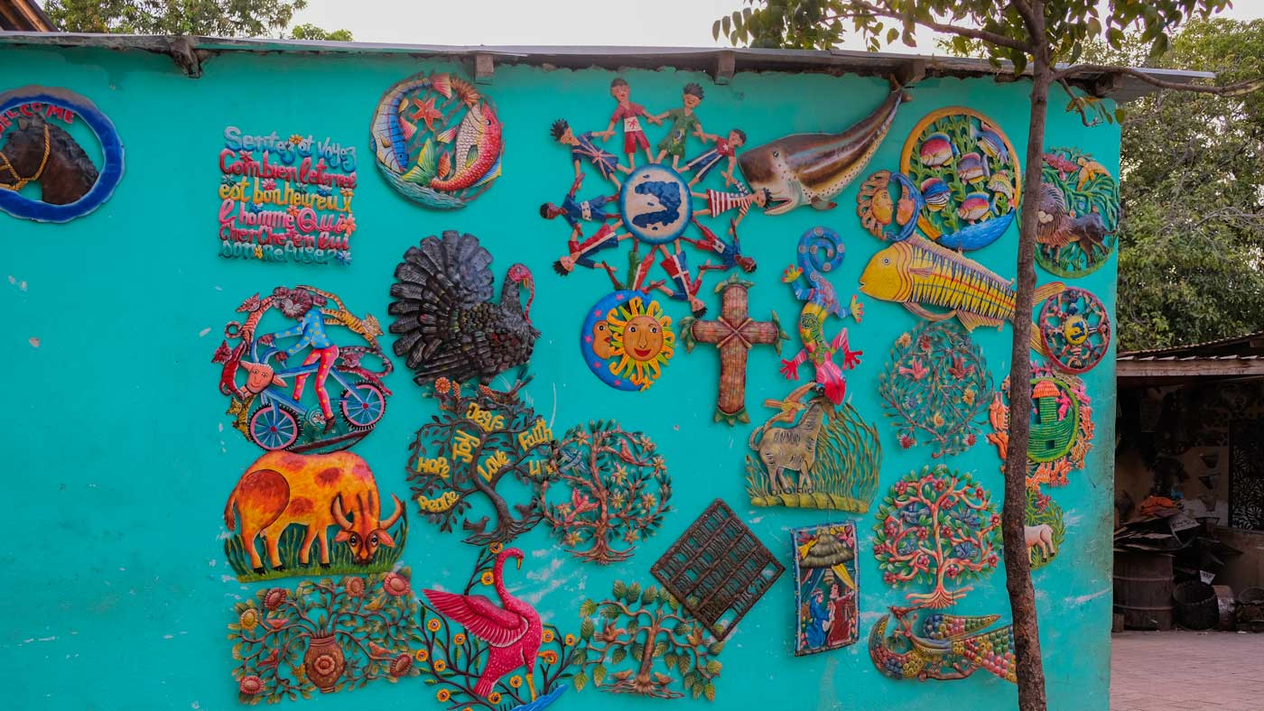 Colorful metal artwork on blue wall in Village Noailles, Haiti