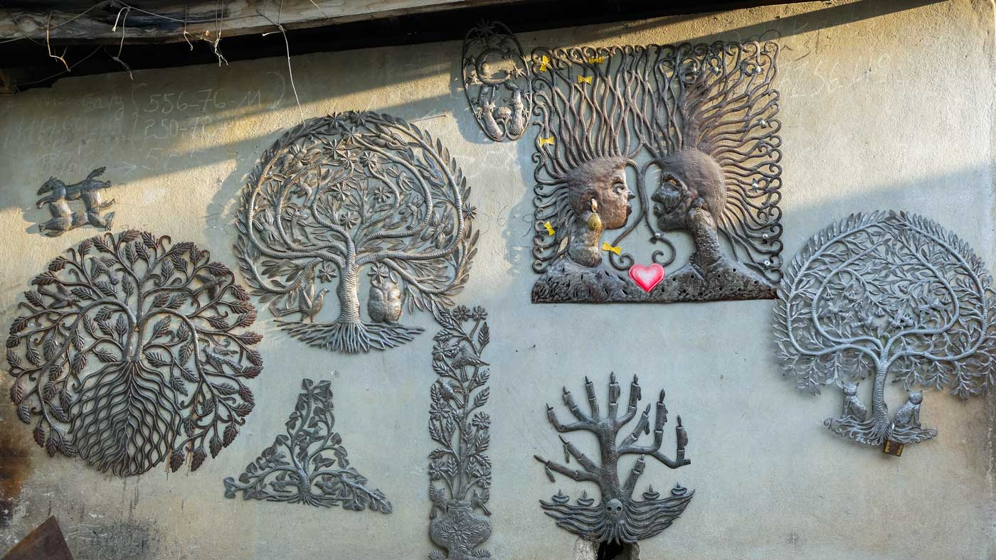Metal artworks hang on a wall in Village Noailles, Haiti