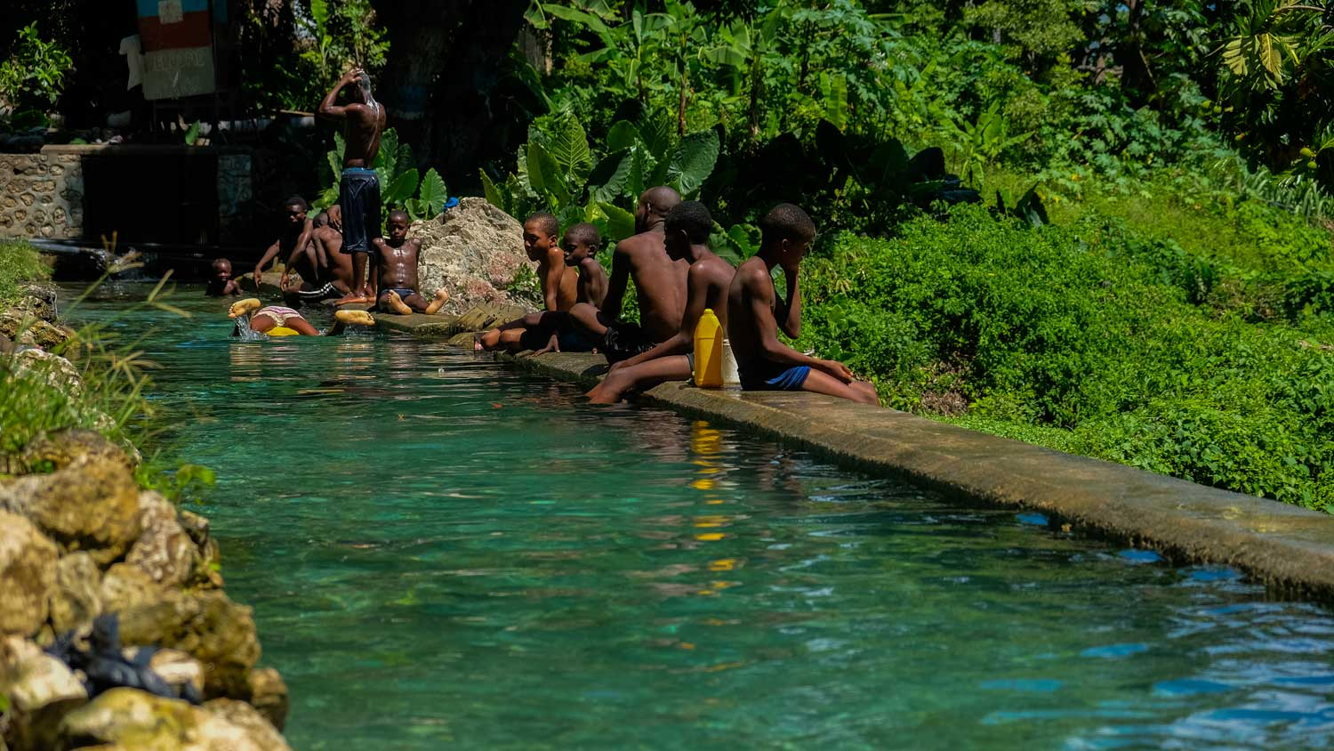 People swimming and sitting on the side of the water pools at Kay Piat, Montrouis, Haiti